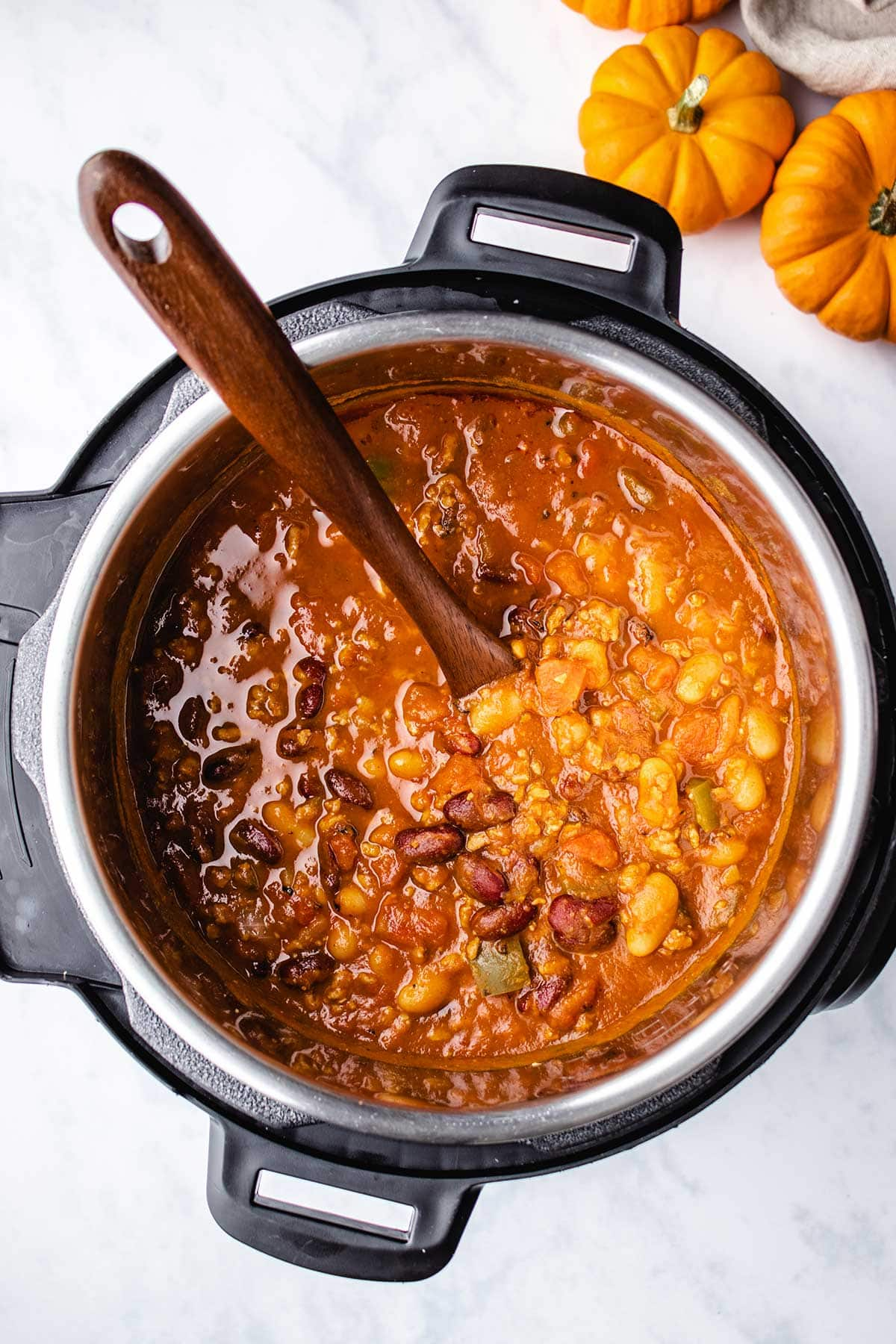 Pumpkin Turkey Chili in an Instant Pot being stirred with a wooden spoon.