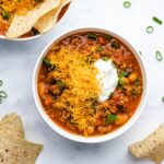 Pumpkin Turkey Chili in two white bowls garnished with green onion, grated cheese, sour cream and corn chips