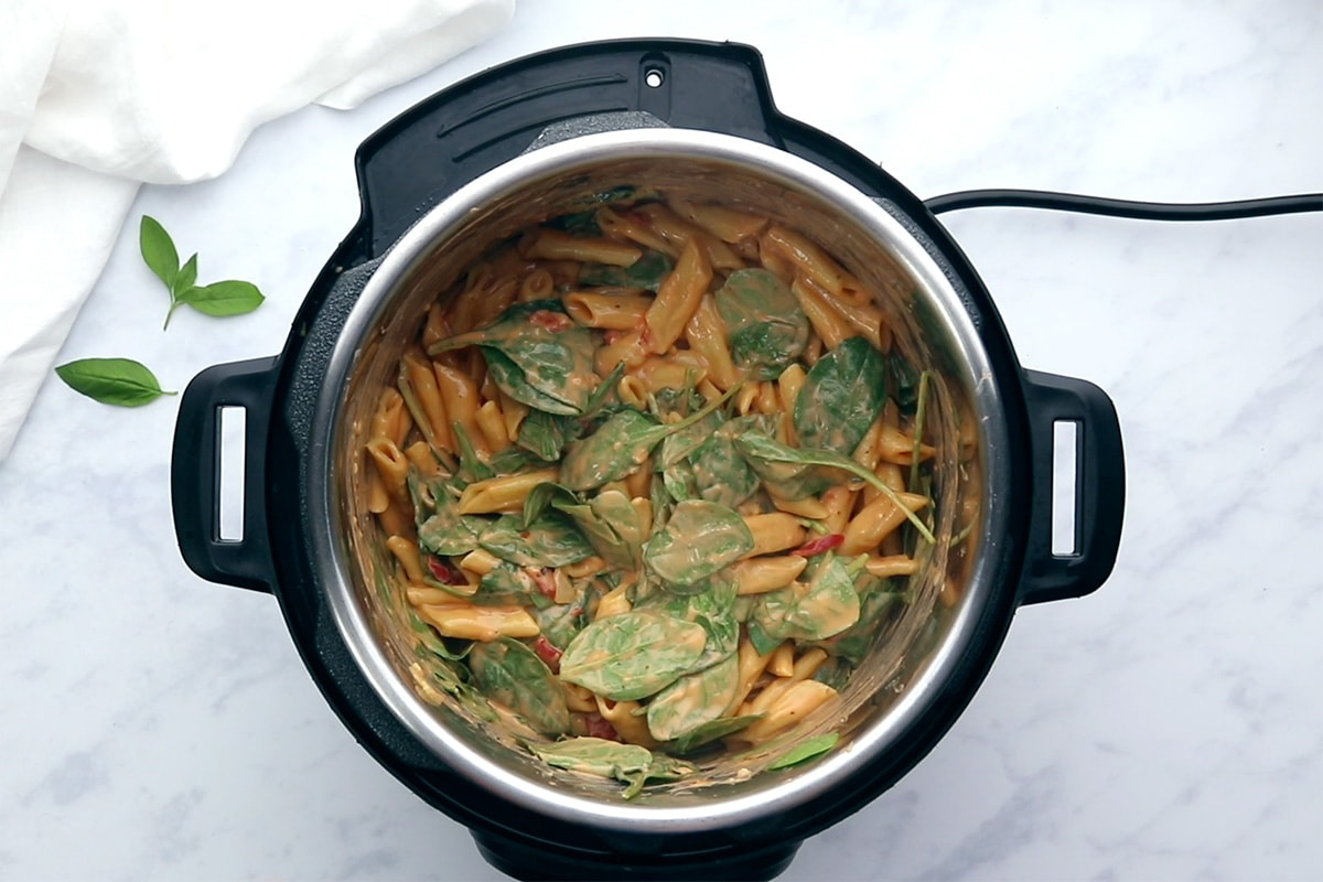Baby spinach stirred into creamy vegan pasta in an Instant Pot.