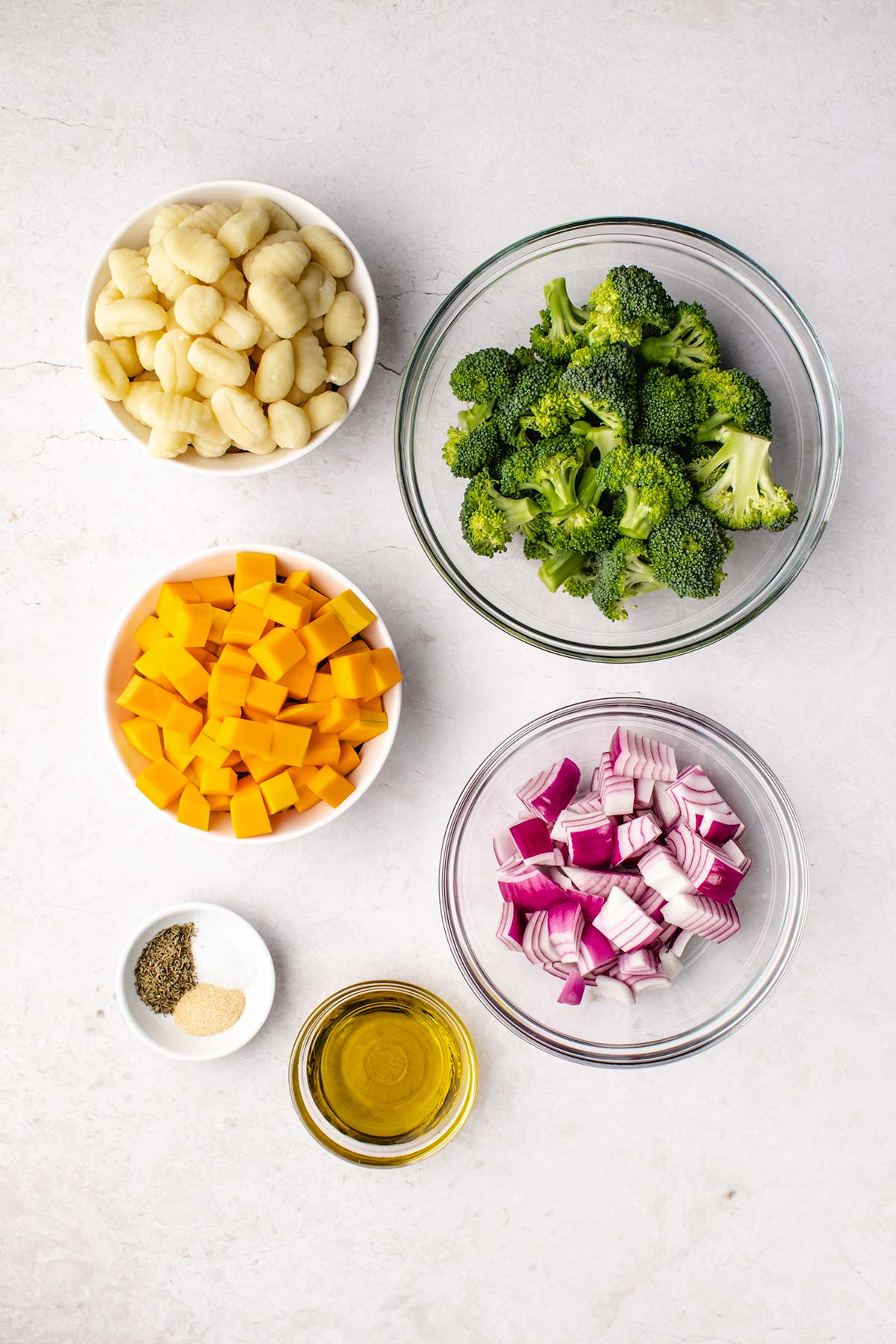 ingredients for sheet pan gnocchi in small bowls viewed from overhead