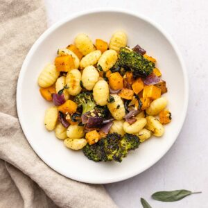roasted gnocchi and vegetables on a white plate next to a brown linen and sage leaves