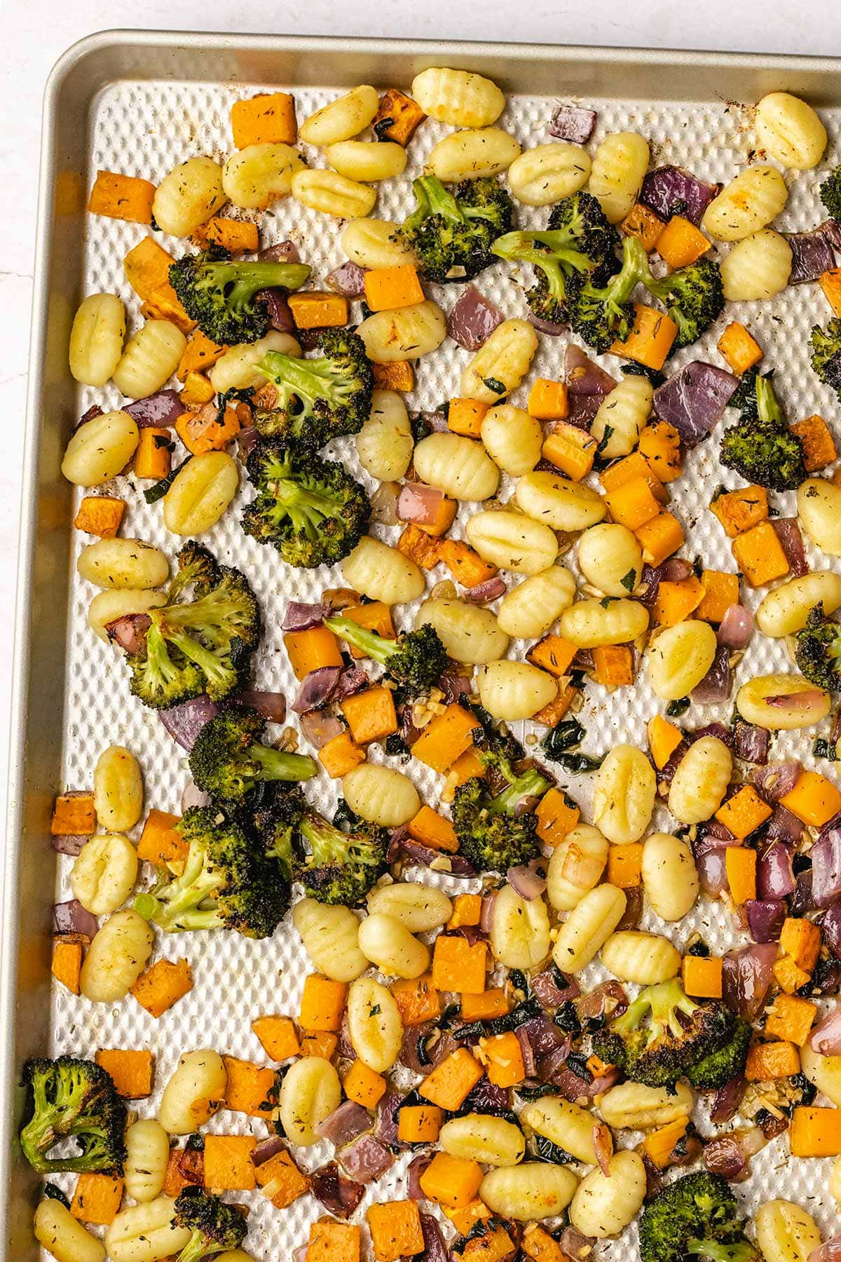 roasted gnocchi, butternut squash, broccoli and red onion on a sheet pan