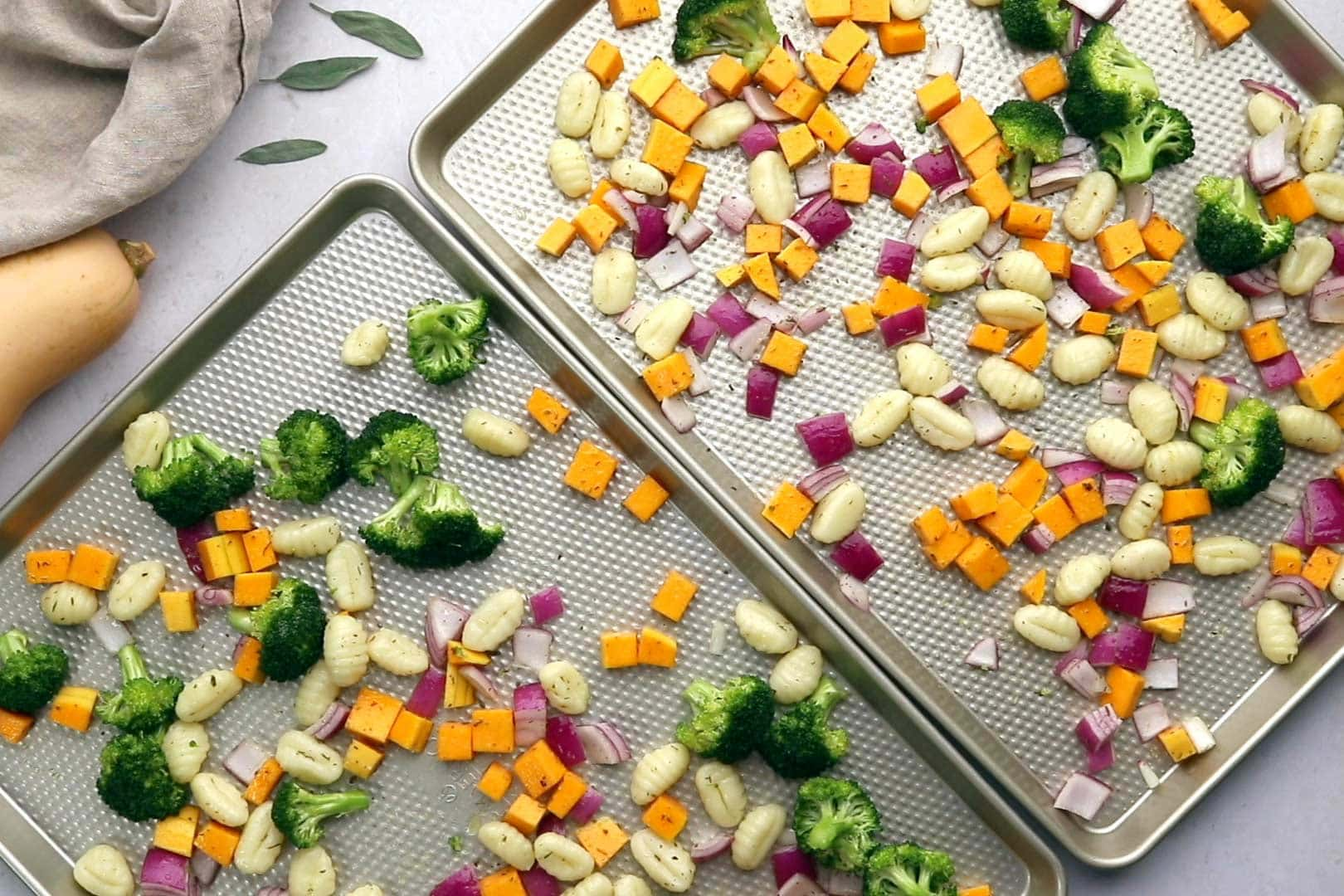 gnocchi, broccoli, butternut squash and red onion spread out on two sheet pans