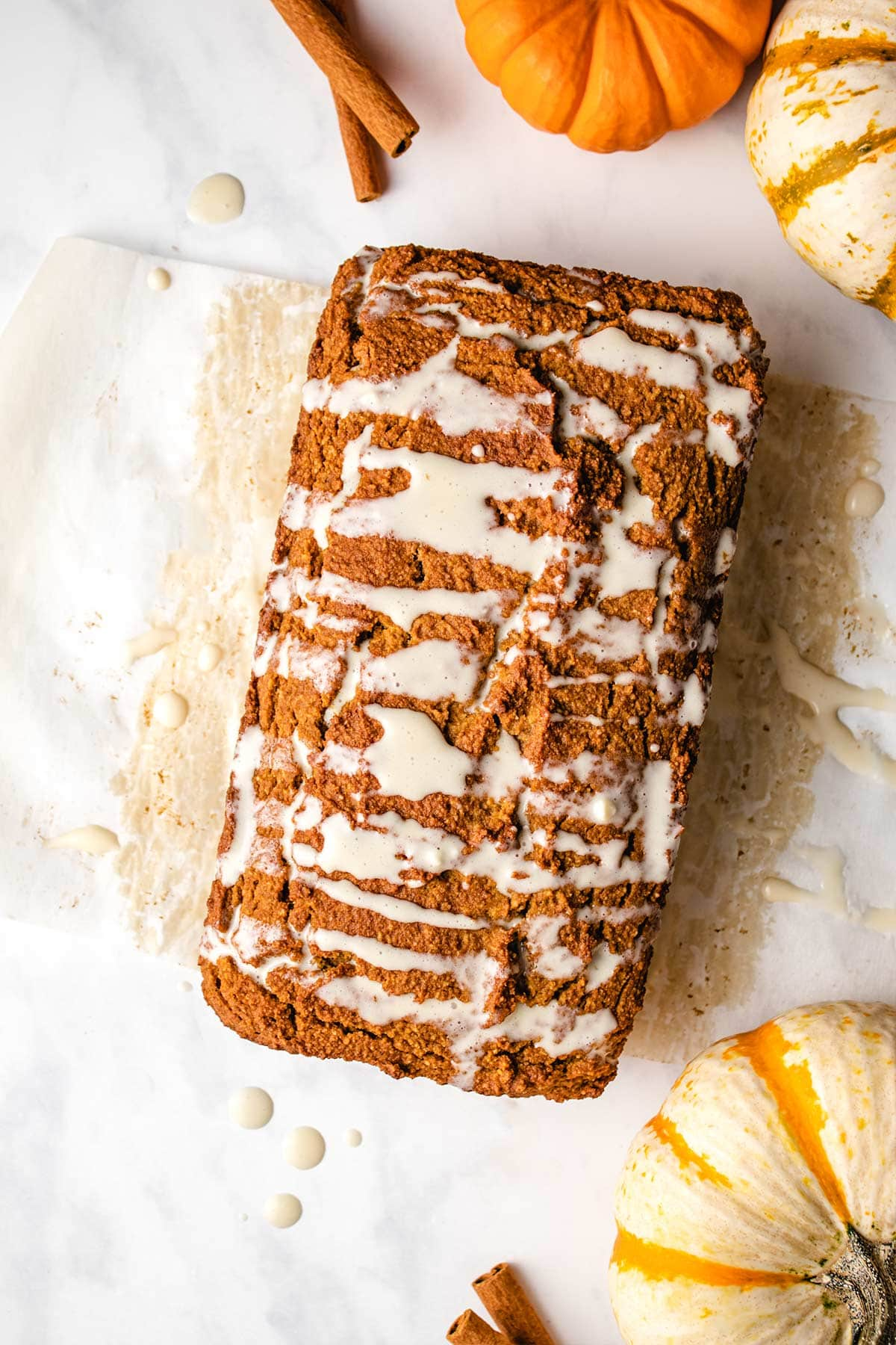 Almond flour pumpkin bread with cream cheese glaze on parchment paper.
