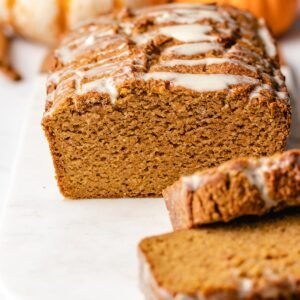 A cut loaf of almond flour pumpkin bread viewed head on with pumpkins in the background.