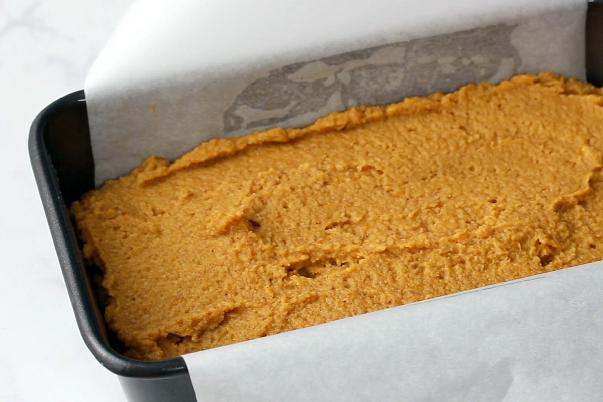 Almond Flour Pumpkin Bread batter in a loaf pan lined with parchment paper.