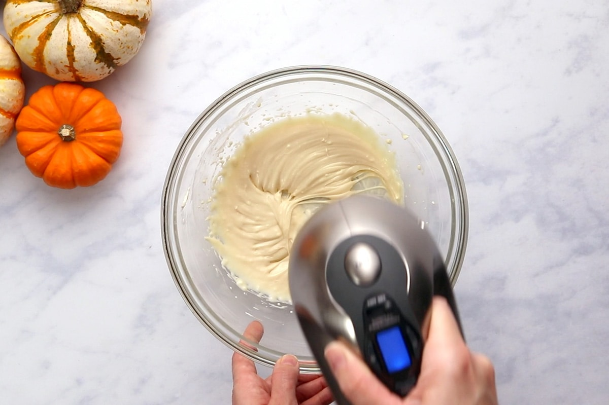 Making maple cream cheese glaze in a glass bowl with a hand mixer.