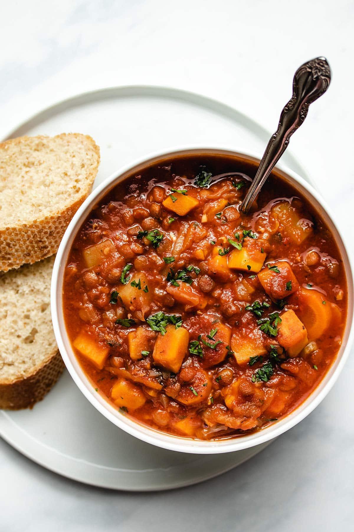 Lentil soup in a white bowl garnished with fresh parsley, on top of a white plate with two slices of crusty bread.