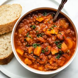 Lentil Soup garnished with fresh parsley in a white bowl next to sliced crusty bread.