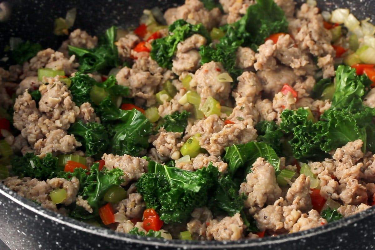 Gekochte gemahlene italienische Wurst, Grünkohl, roter Pfeffer, Zwiebel und Sellerie in einer schwarzen Pfanne.