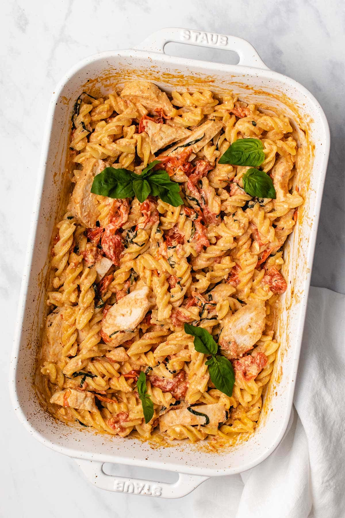 Baked Feta Chicken Pasta in a white casserole dish garnished with fresh basil.