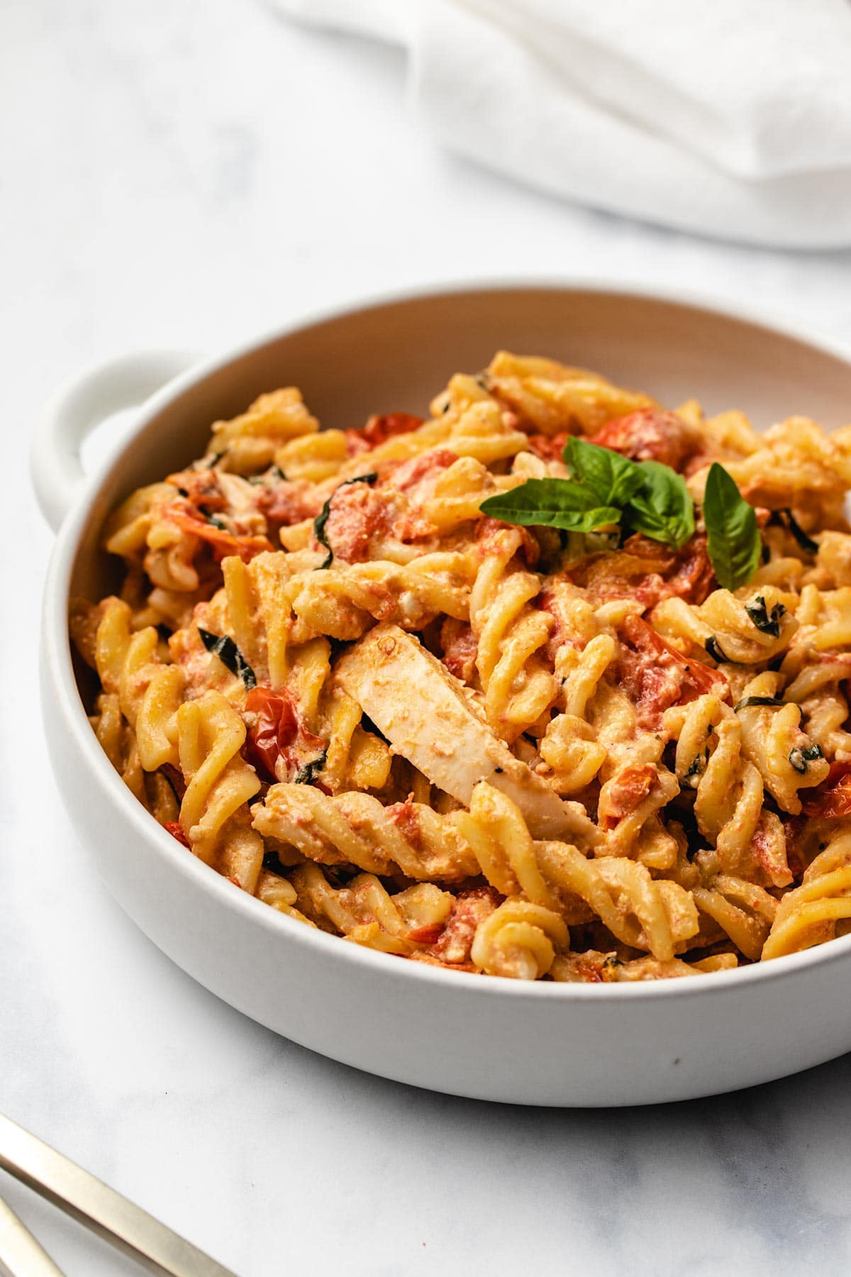 Feta Chicken Pasta in a white bowl garnished with fresh basil.