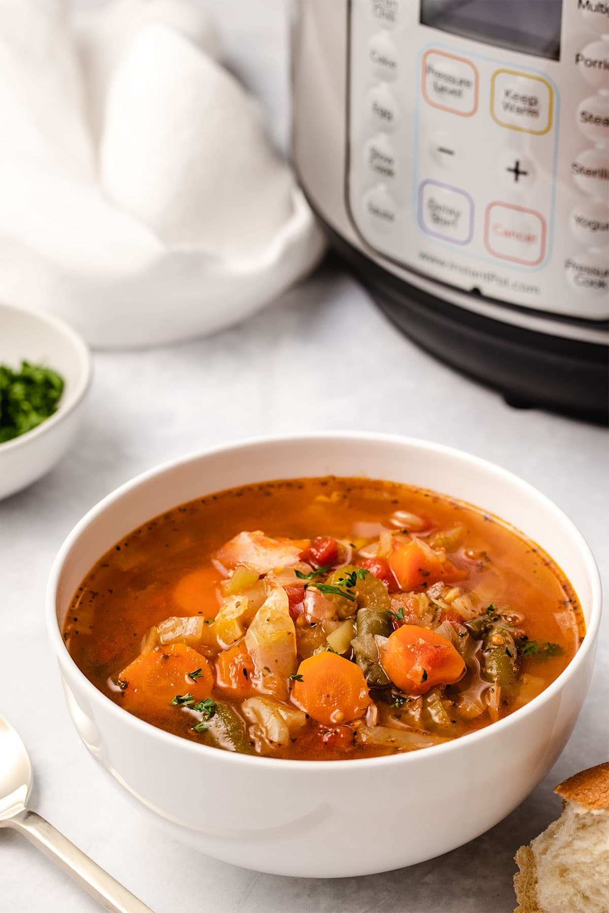 Cabbage Soup in a white bowl placed in front of an Instant Pot.