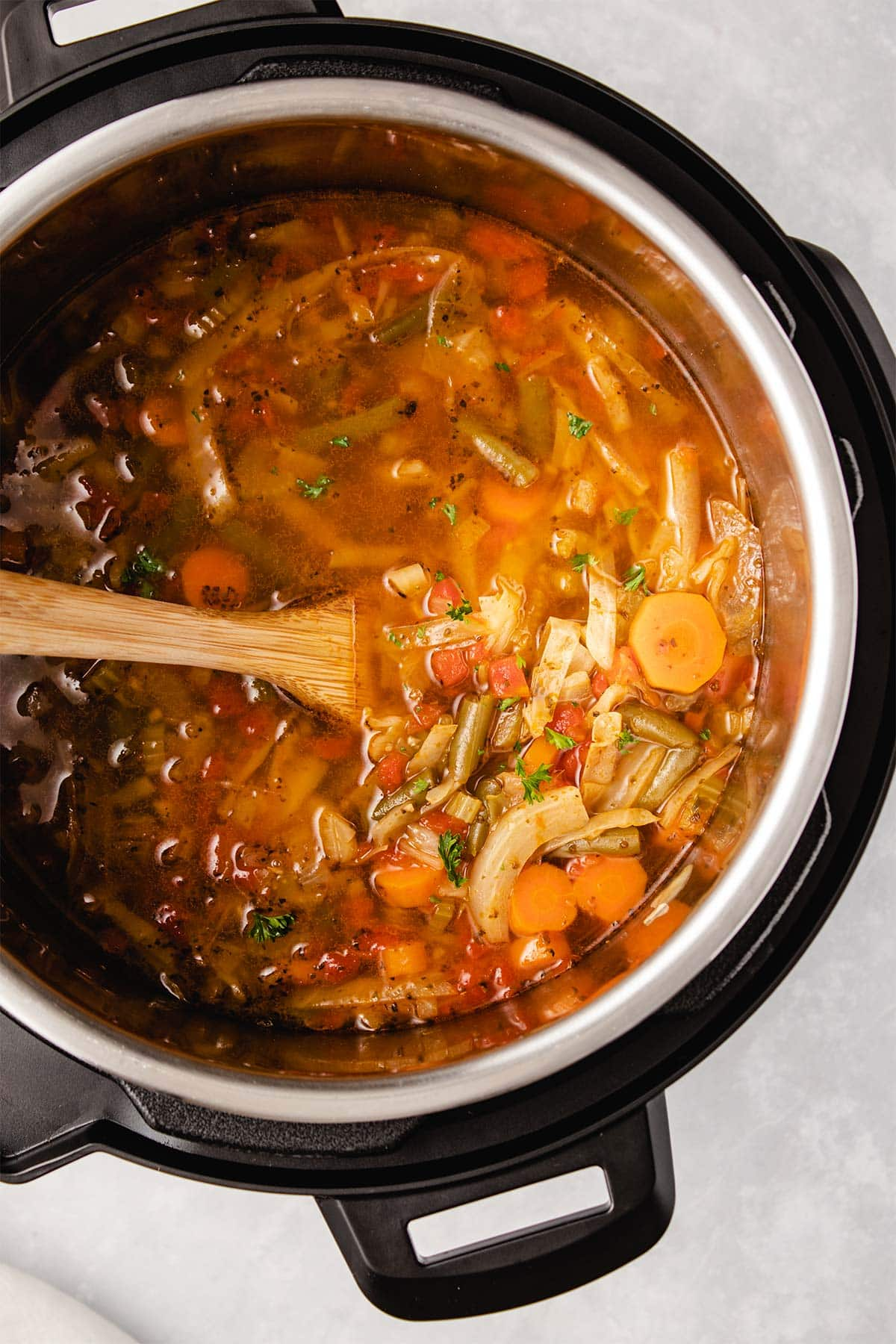 Cabbage Soup in an Instant Pot being stirred with a wooden spoon.