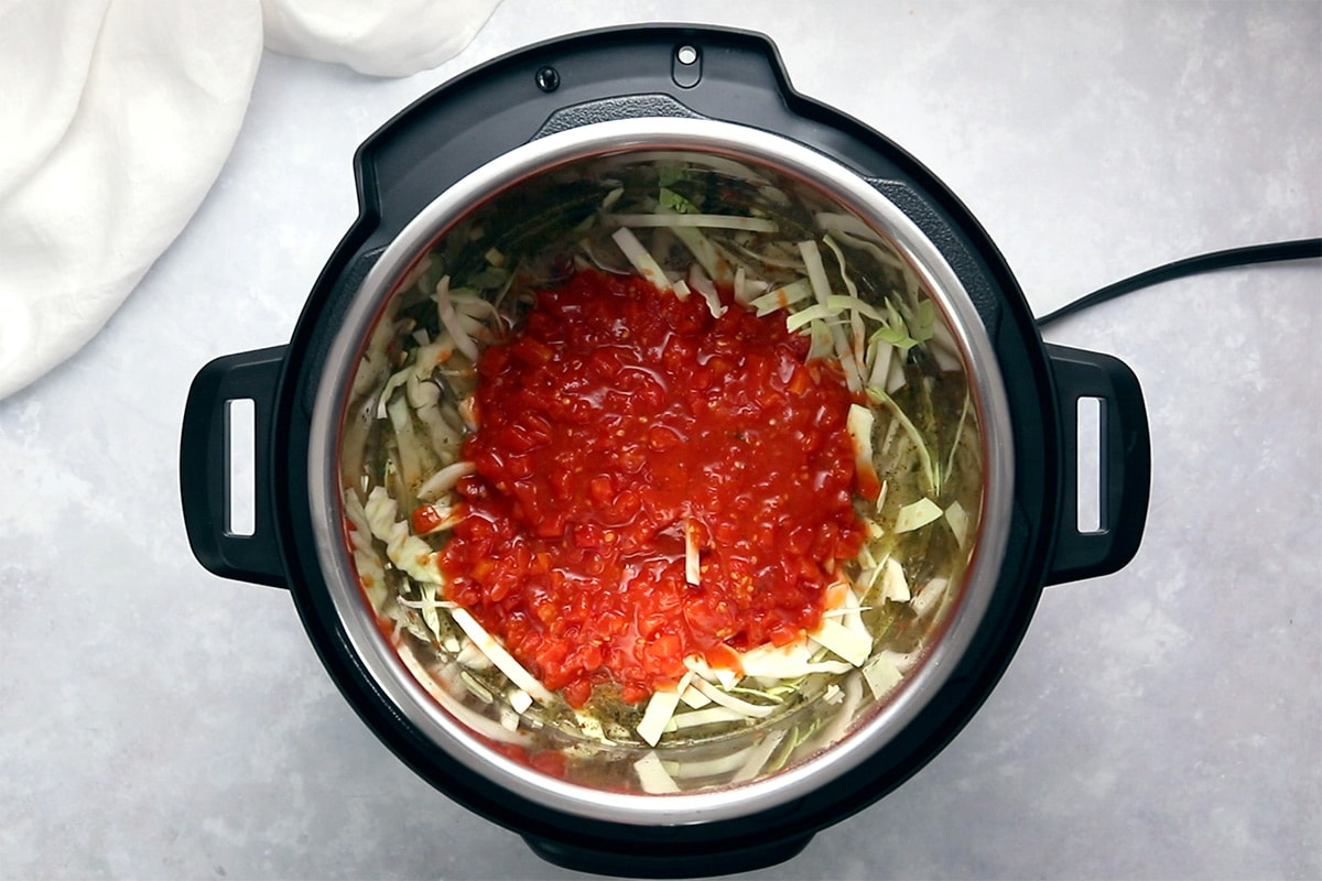 Canned diced tomato layered on top of cabbage in and Instant Pot viewed from overhead.