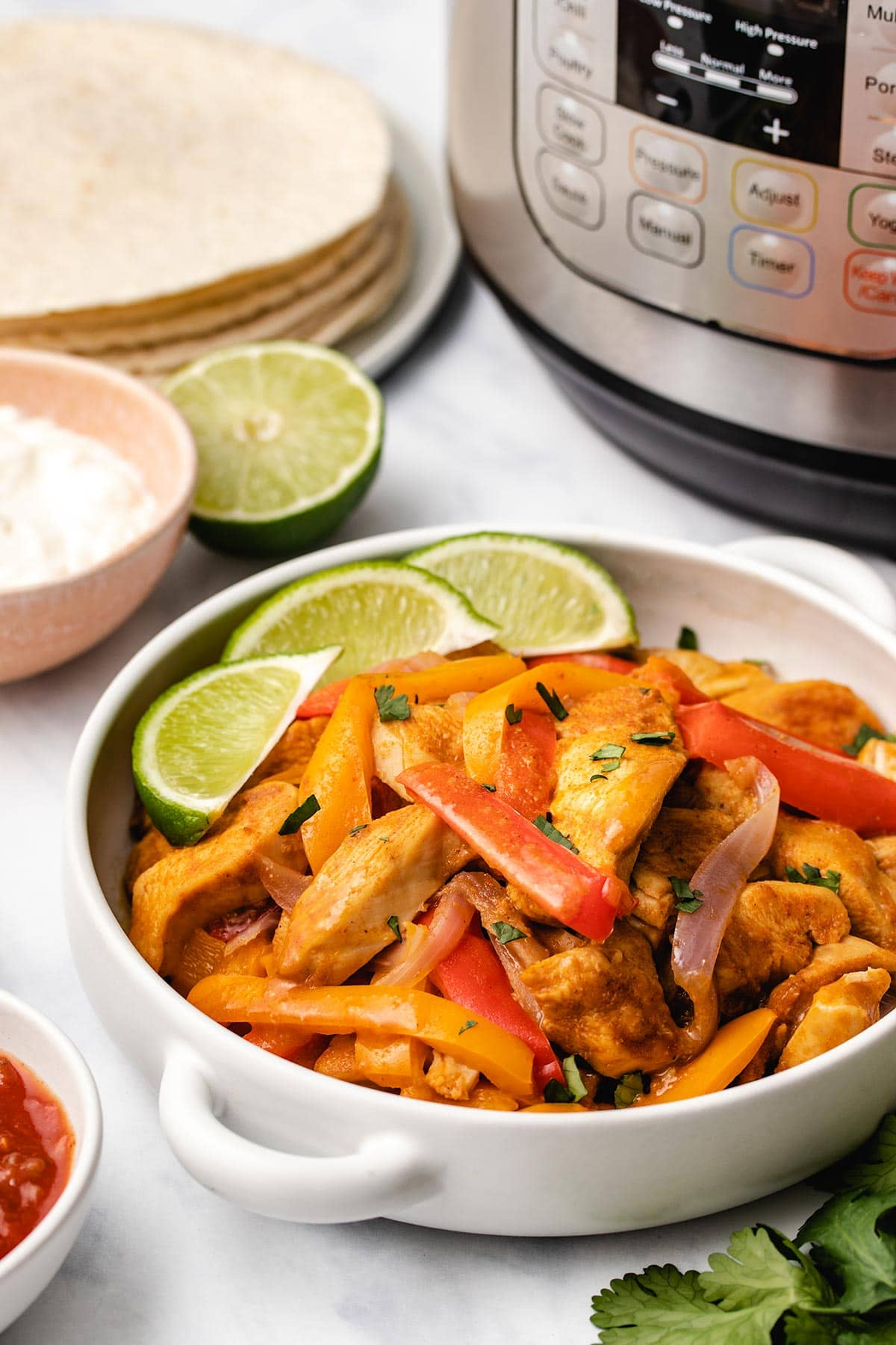 Instant Pot Chicken Fajitas in a white serving bowl with handles, garnished with lime and chopped cilantro.