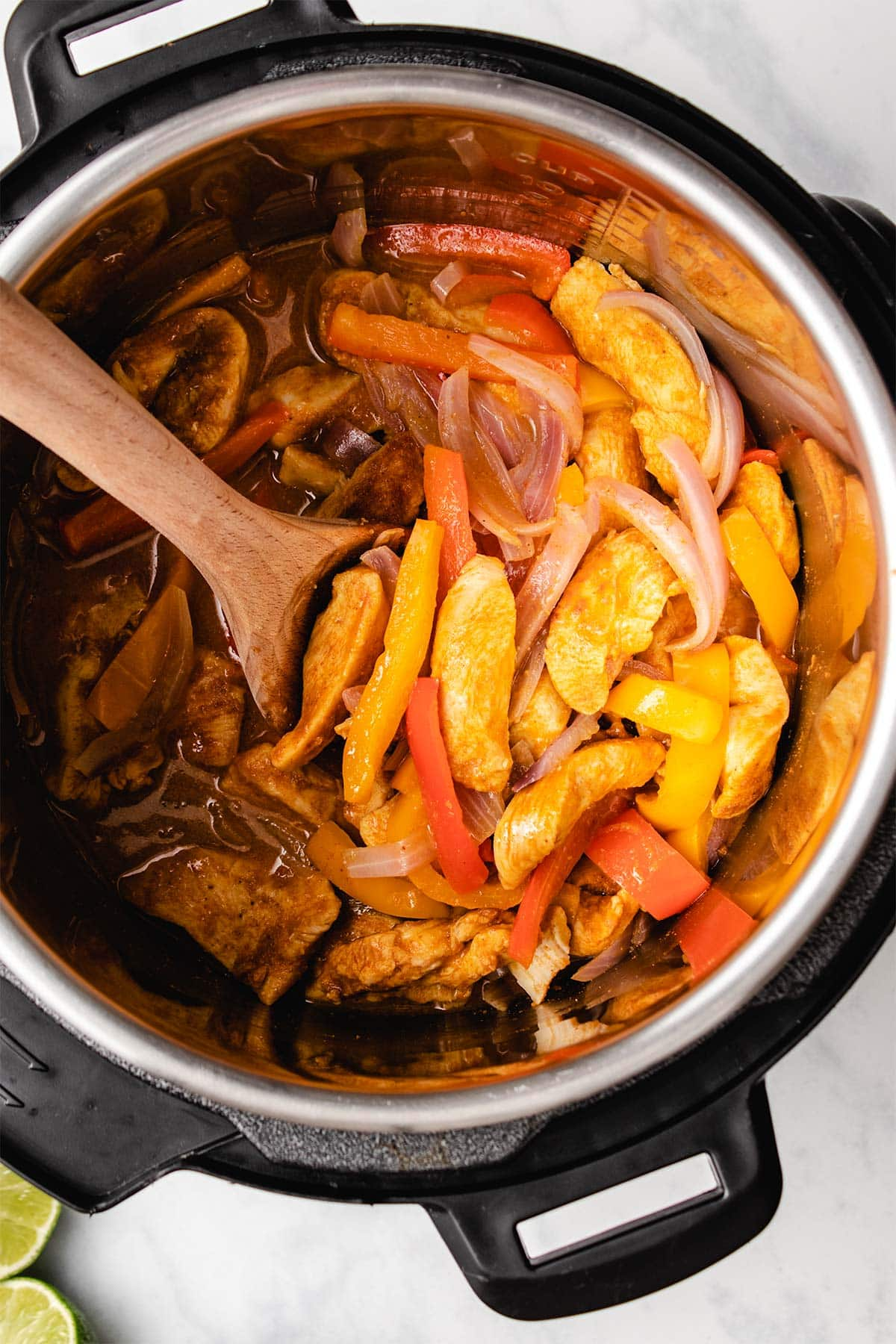 Chicken fajita filling in an Instant Pot being scooped with a wooden spoon.