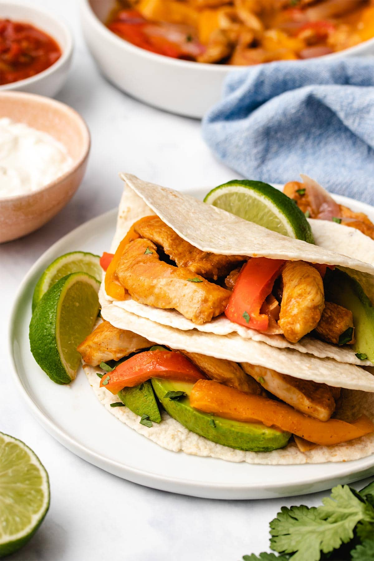 Instant Pot chicken fajita filling in stacked folded tortillas on a white plate.