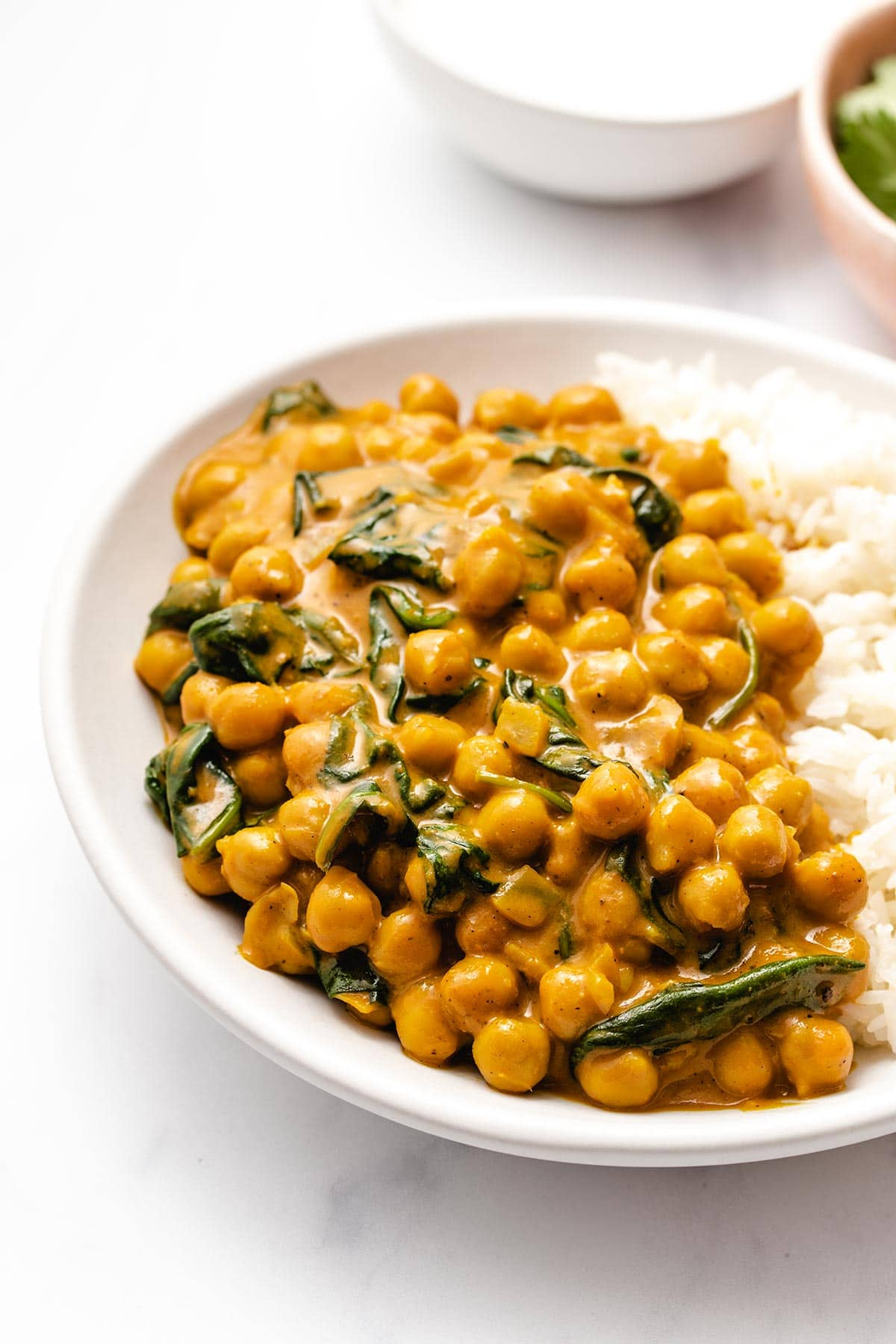 Chickpea spinach curry served with rice on a white plate.