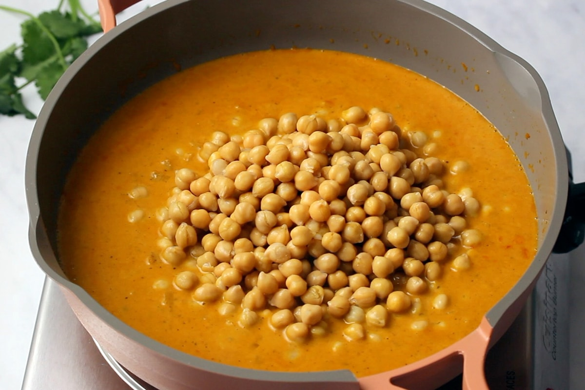 Adding cooked chickpeas to curry in a pink and grey frying pan.