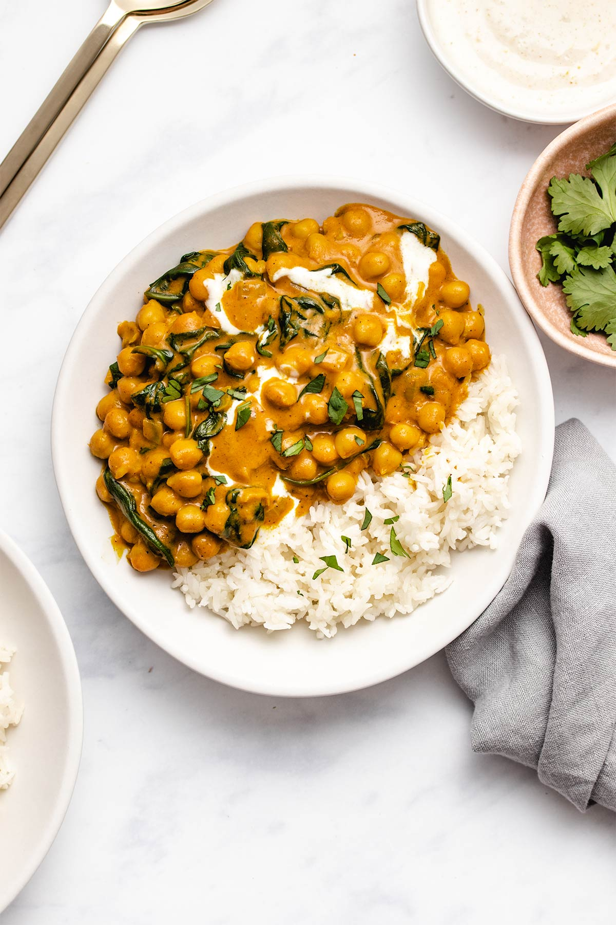 Chickpea spinach curry with a side of rice on a white plate garnished with chopped cilantro.