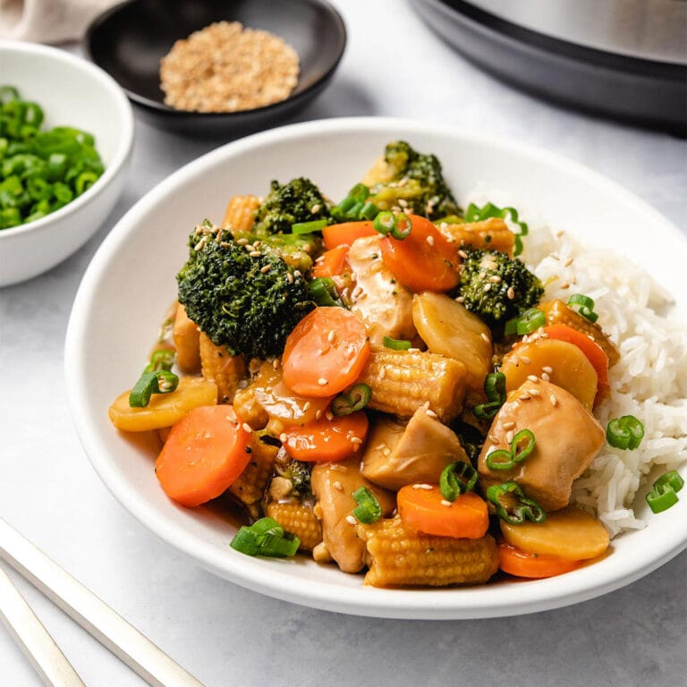 Instant Pot Chicken Stir Fry served with rice on a white plate.