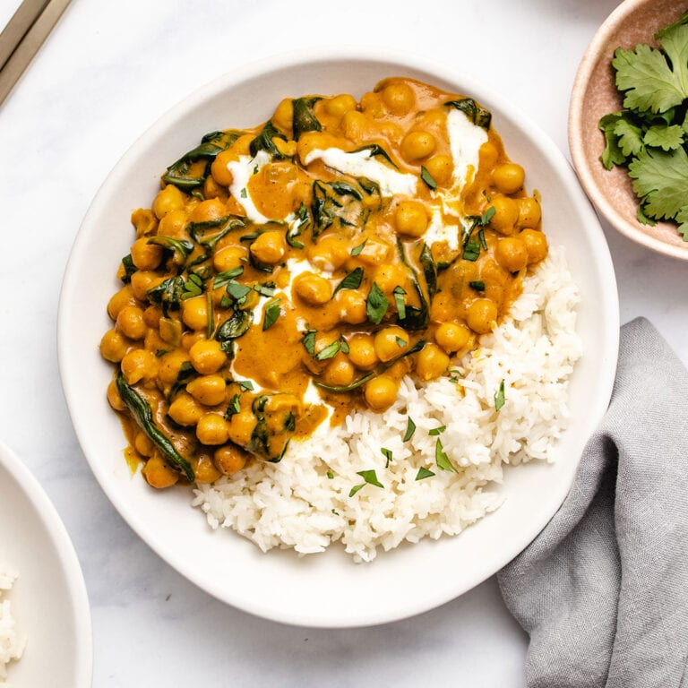 Chickpea Spinach Curry on a white plate served with rice, garnished with yogurt and cilantro.