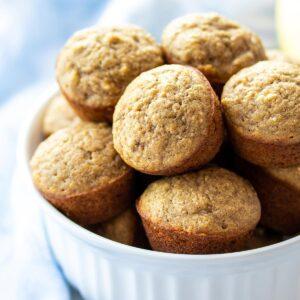 Mini gluten-free banana muffins piled high in a white bowl.