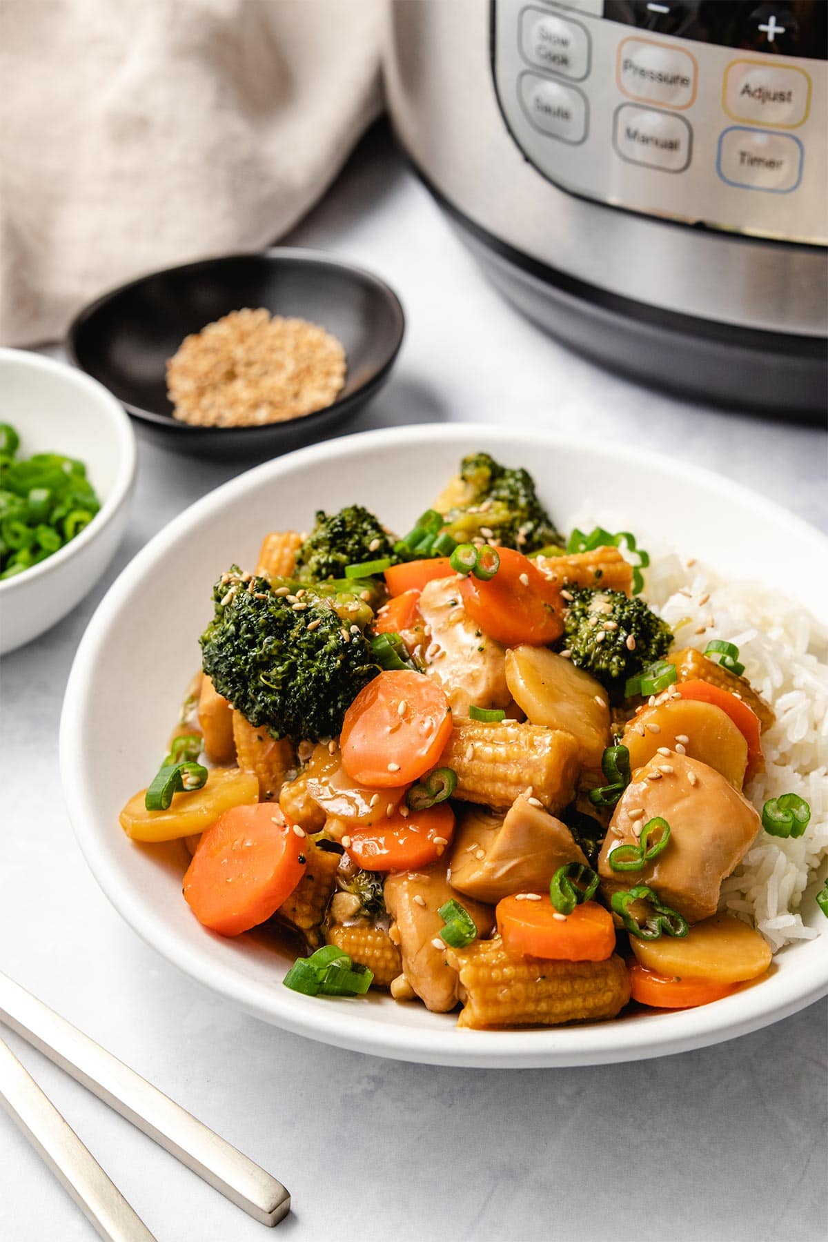 Instant Pot Chicken Stir Fry served with rice on a white plate surround by bowls of garnish and an Instant Pot.
