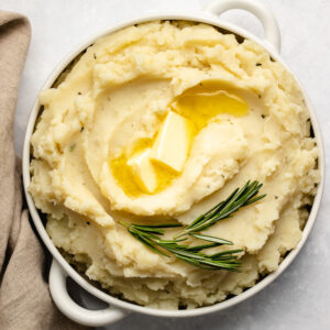 Instant Pot Garlic Rosemary Mashed Potatoes in a white bowl with handles.