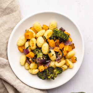 Sheet Pan Gnocchi and Vegetables on a white plate next to a light brown linen.