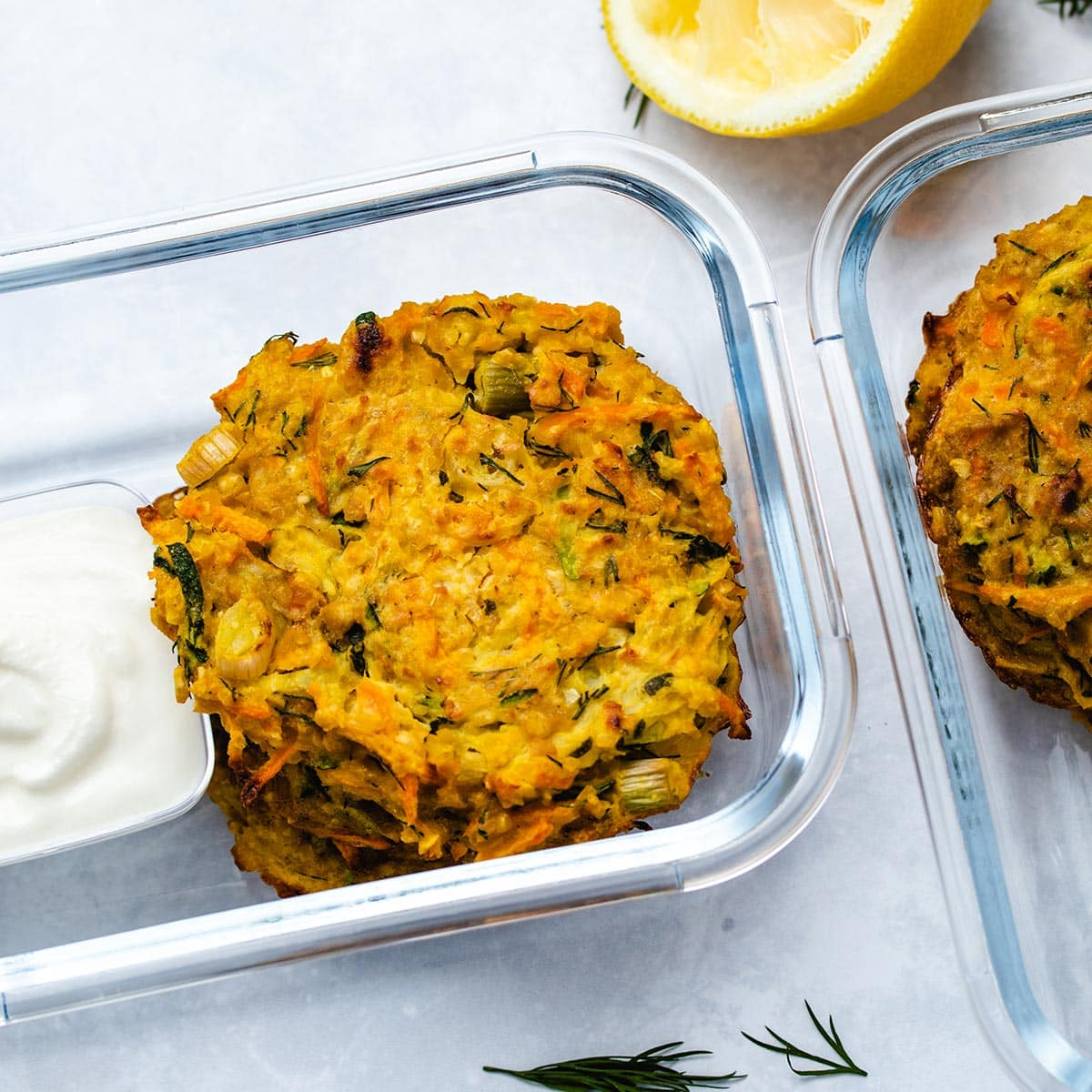 Zucchini Carrot Fritters in glass meal prep containers with a side of Greek yogurt.