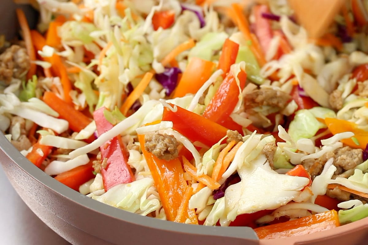 Coleslaw mix, bell peppers and chicken being cooked together in a pink and grey frying pan.