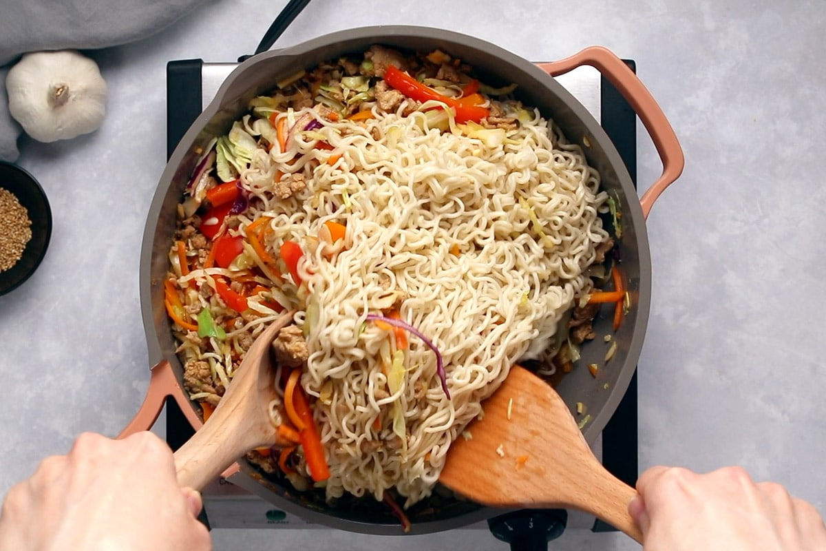 Ramen noodles being mixed into stir-fried chicken and vegetables in a pink and grey frying pan.