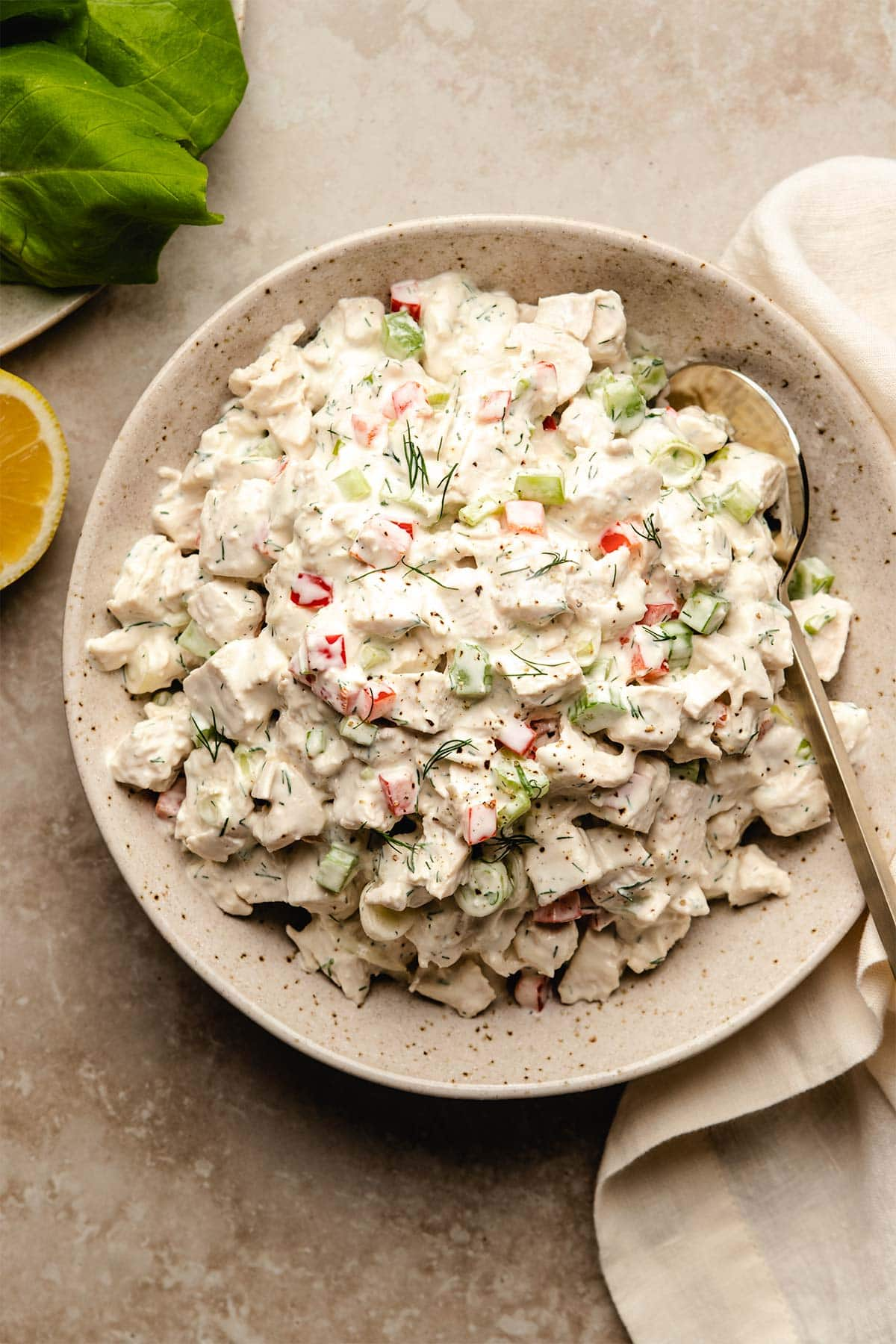 Chicken salad in a beige speckled bowl with a gold spoon tucked in, viewed from overhead.