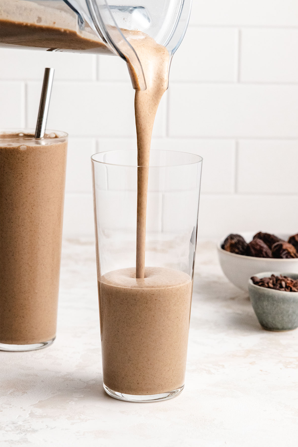Coffee Protein Smoothie being poured from a blender into a tall clear glass.