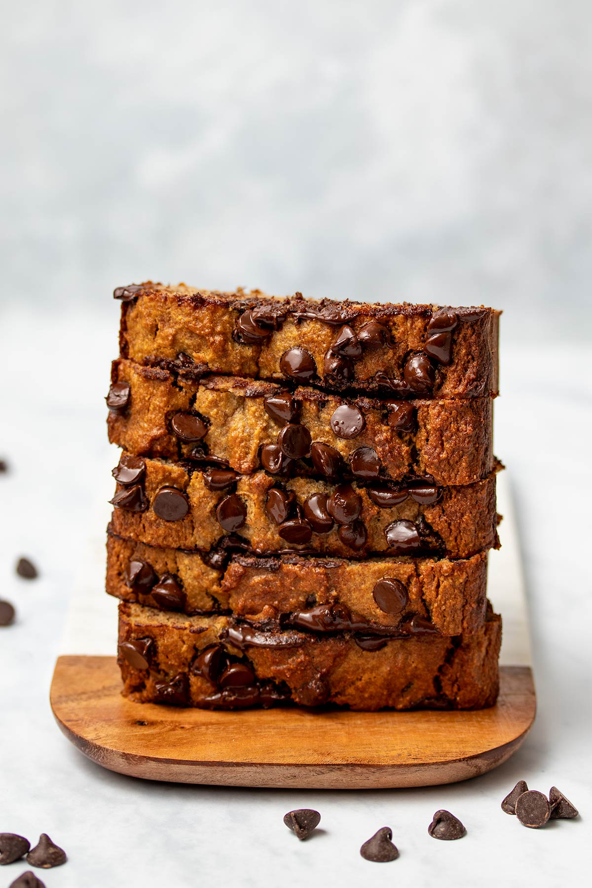 Slices of almond flour banana bread stacked vertically on a wood and marble serving tray, with chocolate chips sprinkled in the foreground.