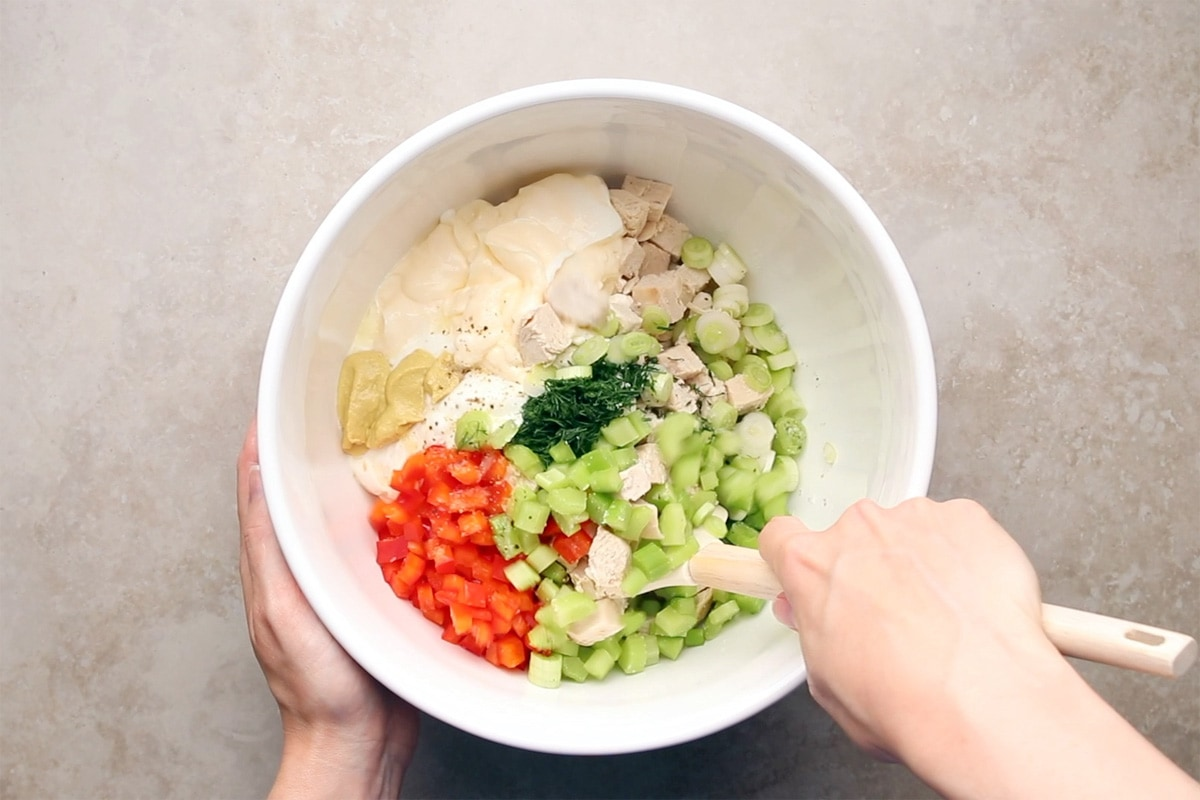 Mixing ingredients for Instant Pot Chicken Salad in a large white bowl.