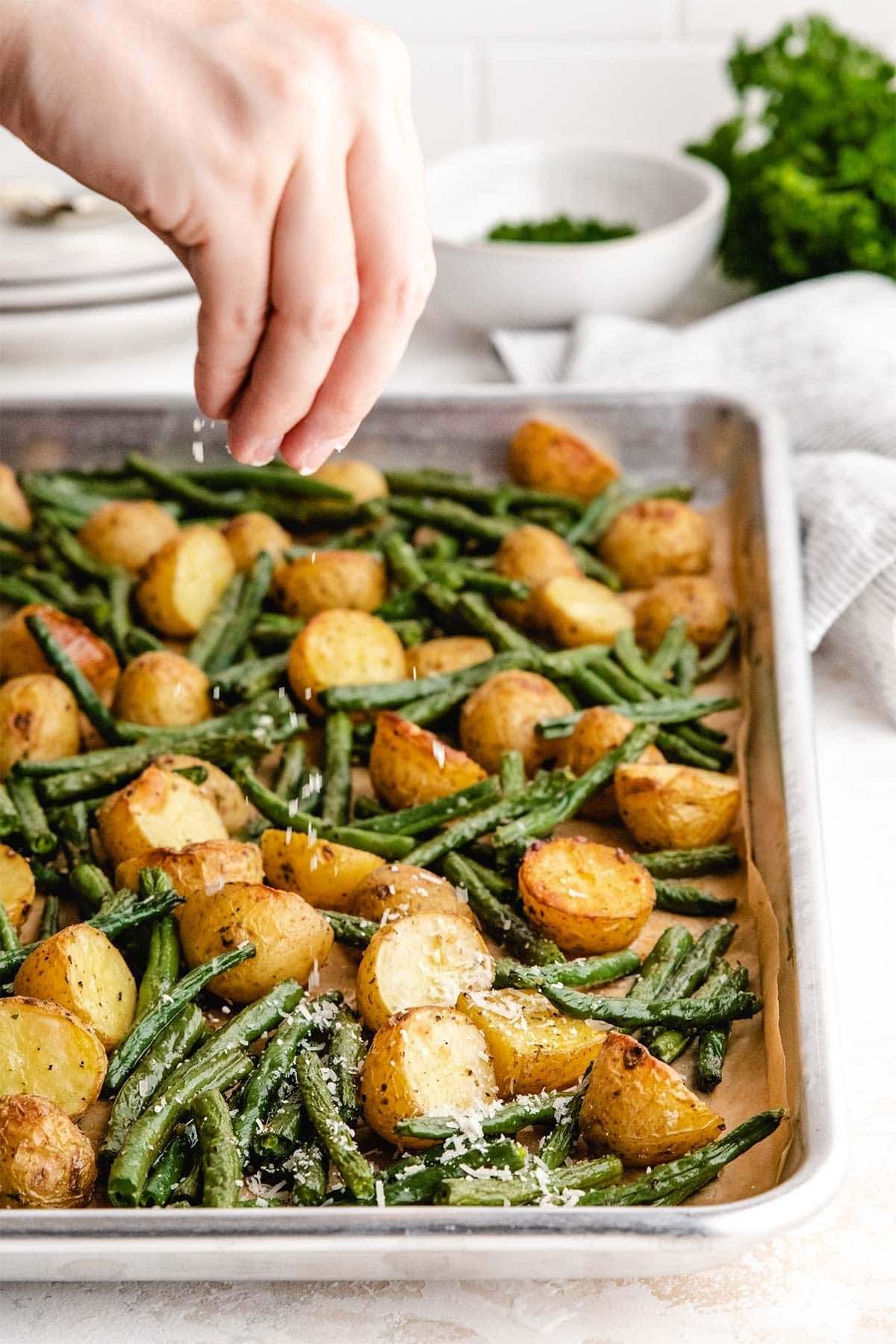 Sprinkling finely grated parmesan cheese onto roasted potatoes and green beans on a sheet pan.