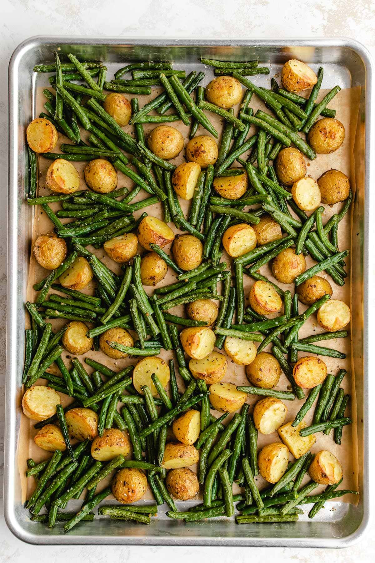 Roasted potatoes and green beans on a parchment-lined baking sheet, viewed from overhead.