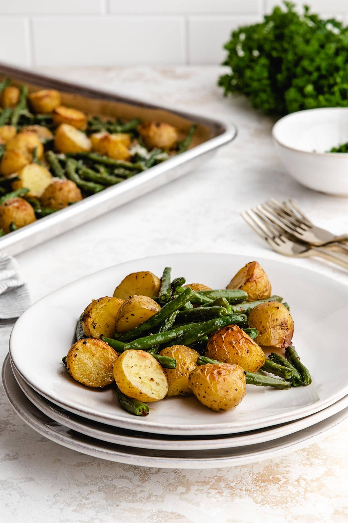 A serving of roasted potatoes and green beans on a stack of three white plates.
