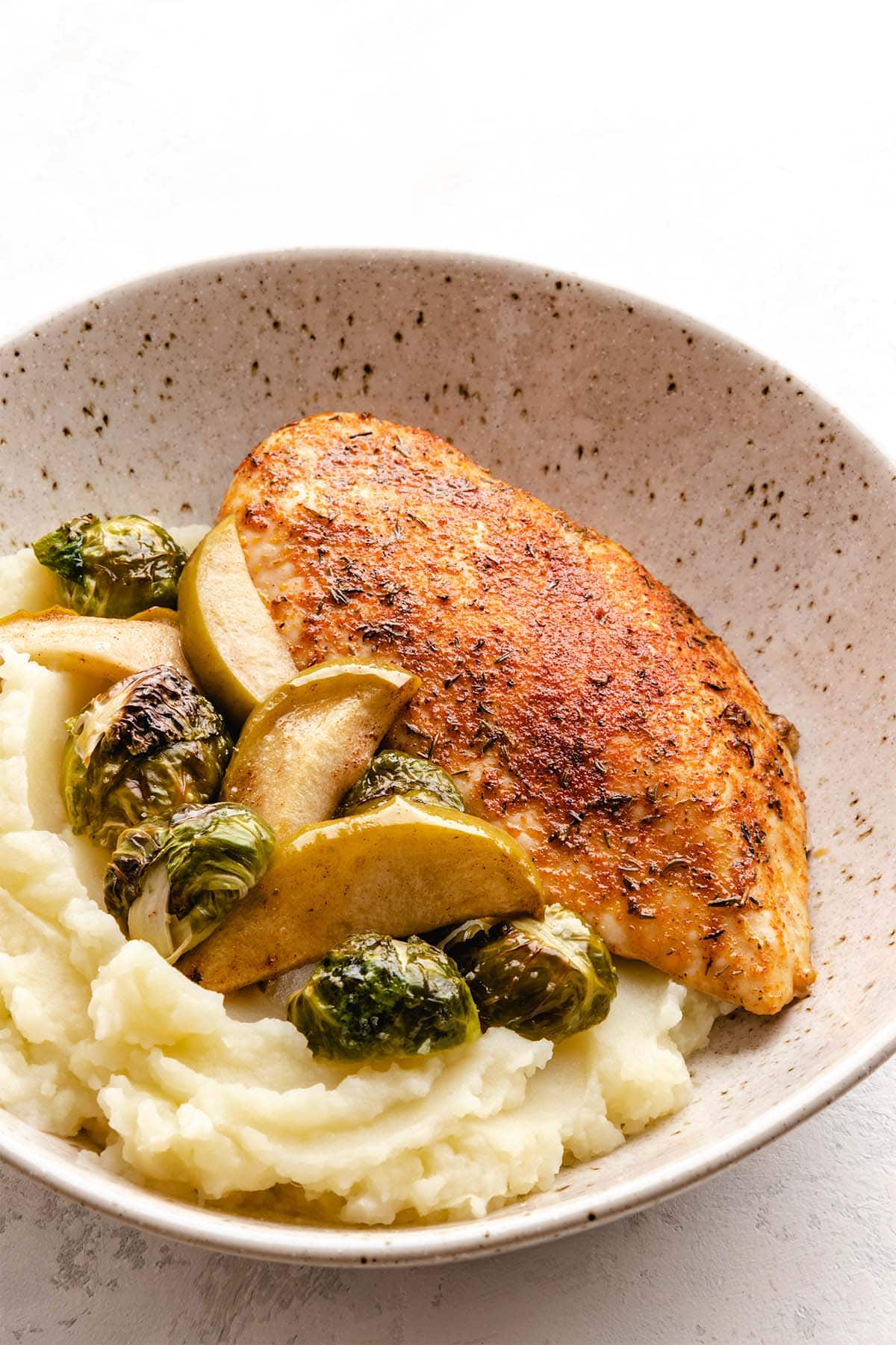 Roasted chicken breast with brown sugar seasoning, served with sliced apples, Brussels sprouts and mashed potatoes in a beige speckled low bowl.