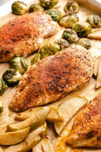 Roasted chicken breast with brown sugar seasoning, surrounded by apple slices and Brussels sprouts on a parchment-lined sheet pan.