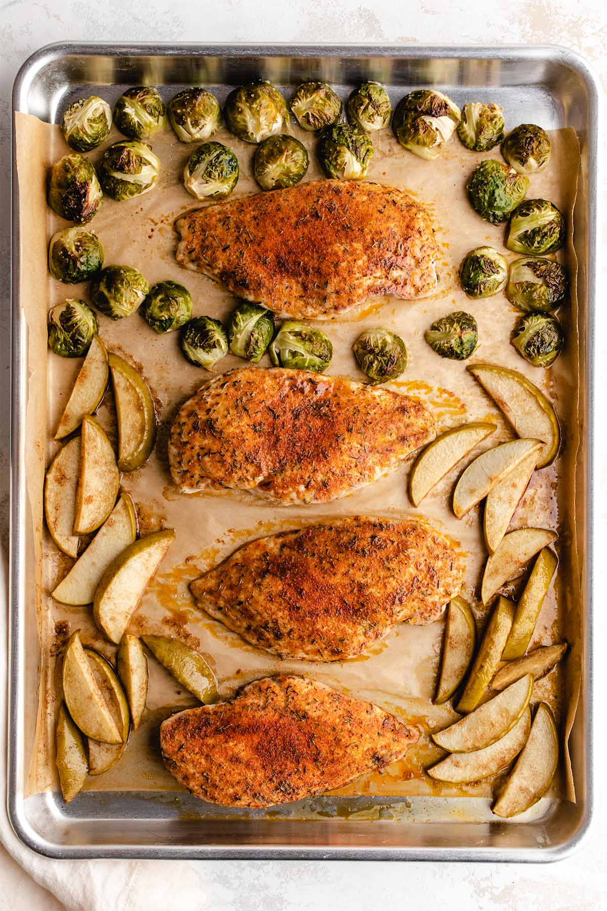 Four roasted chicken breasts with Brussels sprouts and apple slices on a baking sheet.