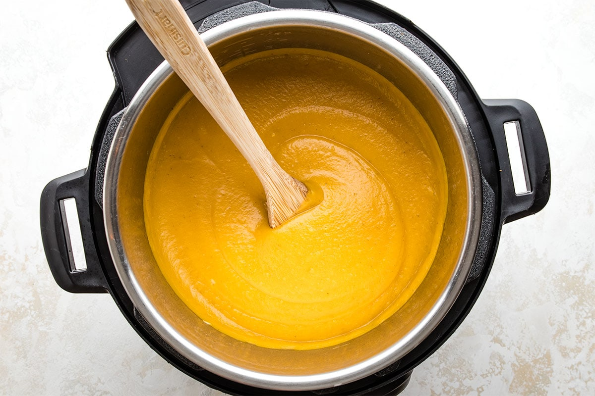Butternut Squash Soup being stirred in an Instant Pot with a wooden spoon, viewed from overhead.