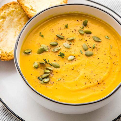 Butternut squash soup in a white bowl with a black rim, garnished with pumpkin seeds, thyme and black pepper, served with two buttered baguette slices.