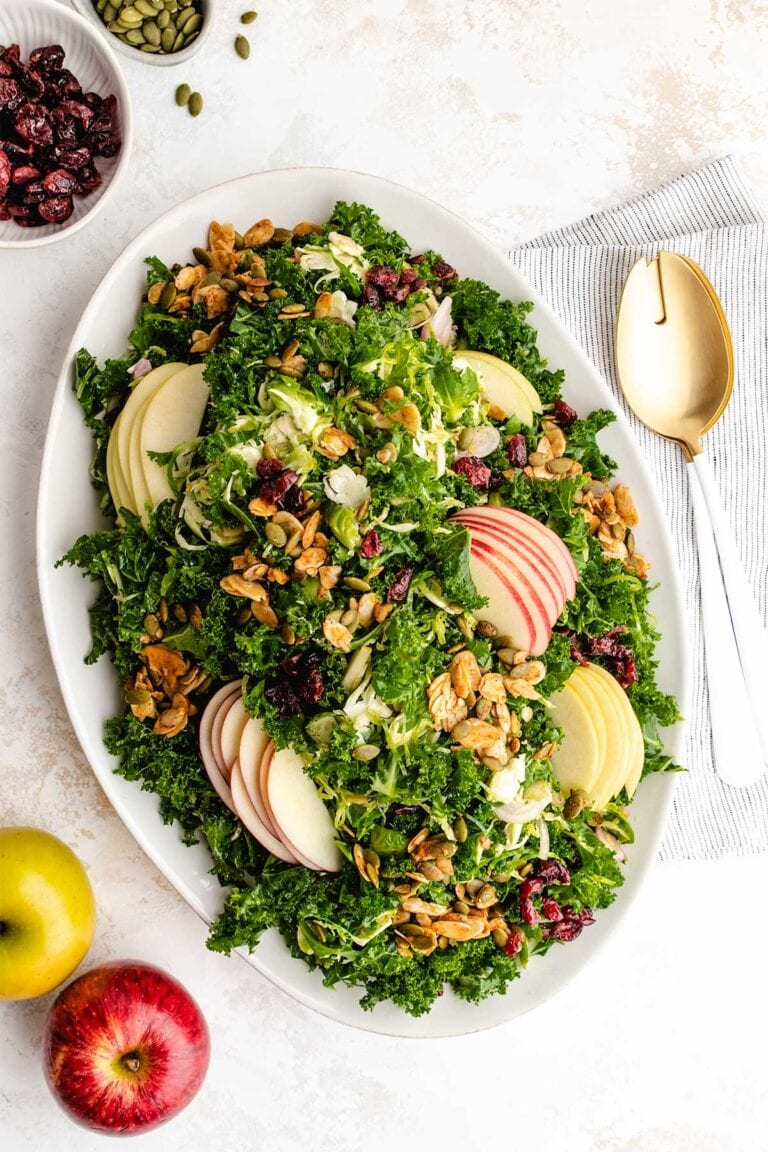 Kale and Brussels Sprouts Salad on a shallow, white oval serving dish, next to apples, pepitas, dried cranberries and serving spoons.