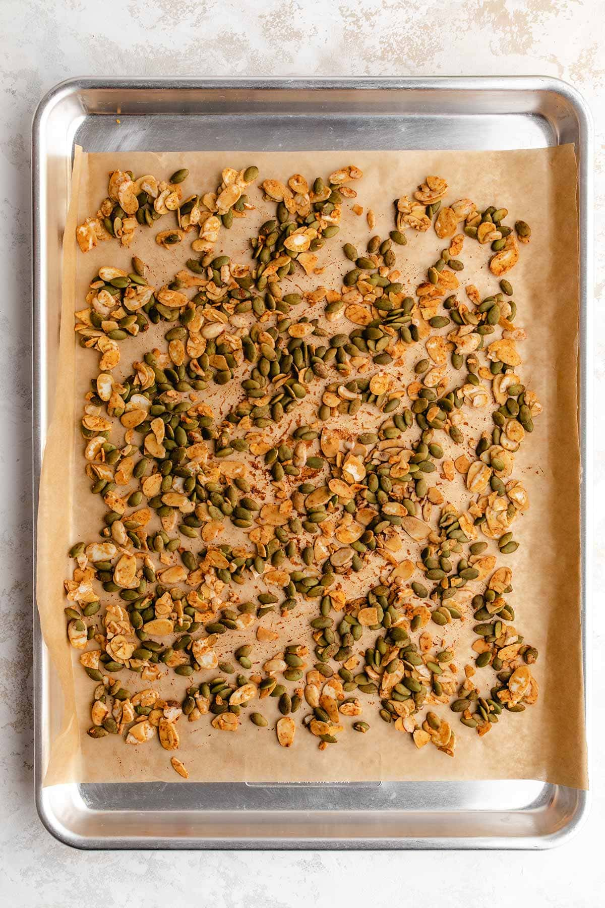 Pepitas and almond slices on a parchment-lined baking sheet, seasoned with paprika, cumin and tamari.