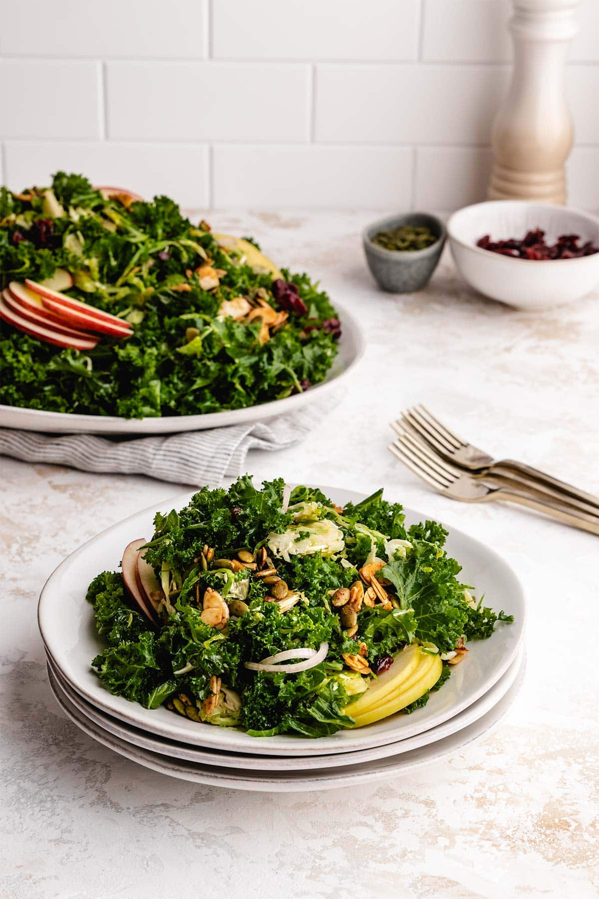 A serving of Kale and Brussels Sprouts Salad on a stack of 3 white plates, in front of the remaining salad on a serving dish.