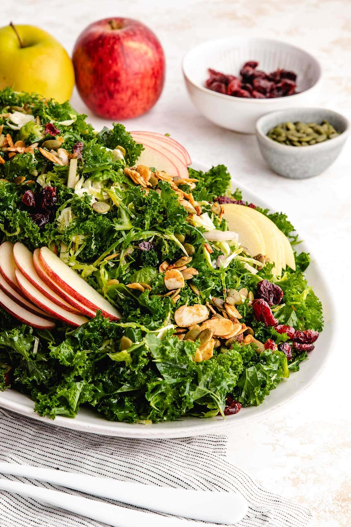 A closeup photo of Kale, Apple and Brussels Sprouts Salad on a white serving dish.